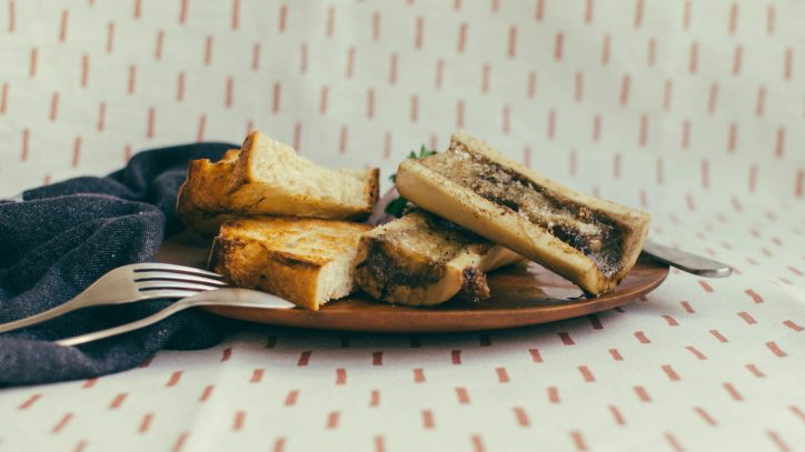 Side view, two pieces of bone marrow and toast on a wood plate against a fabric background - The Mummy