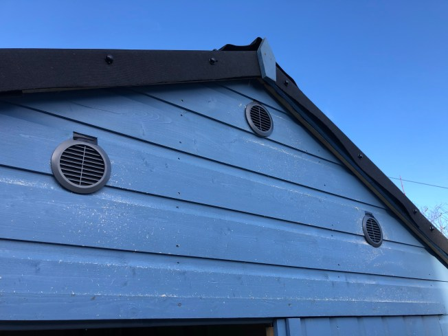 Three circular vents installed on exterior of shed.