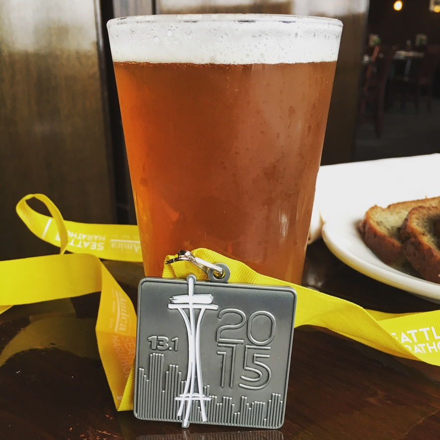 Medal from completing the Seattle half-marathon next to a glass of beer.