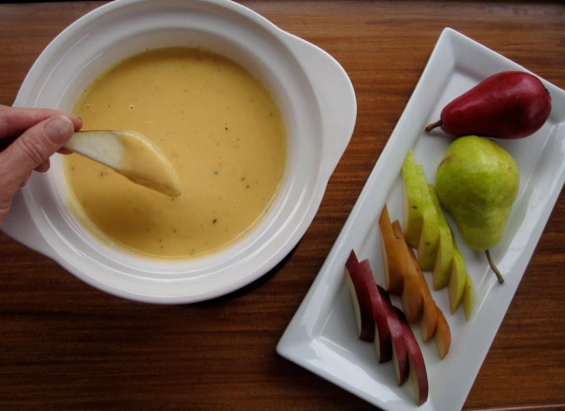 Fondue is a Swiss melted cheese dish served in a communal pot over a portable stove heated with a candle or spirit lamp, and eaten by dipping bread into the cheese using long-stemmed forks.