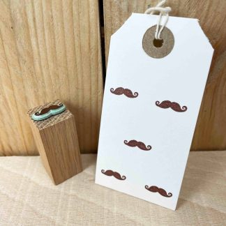 rubber stamp of a moustache stamped with brown ink