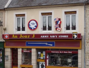 If not for the French signs and architecture of Ste.-Mère-Église, tourist shops such as this army-navy store might have convinced me that I was back in Gettysburg. Sainte-Mère-Église, incidentally, is one of Gettysburg's sister cities. Photo credit to author.