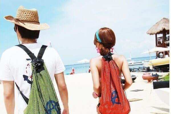 sırt çantası ile sahile yürüyen çift