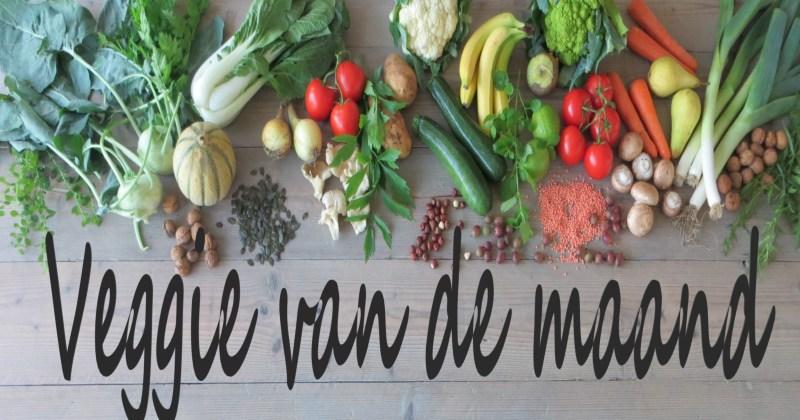 Een tafel vol met groenten, fruit, kruiden, noten en bonen, met daaronder de tekst 'Veggie van de maand'