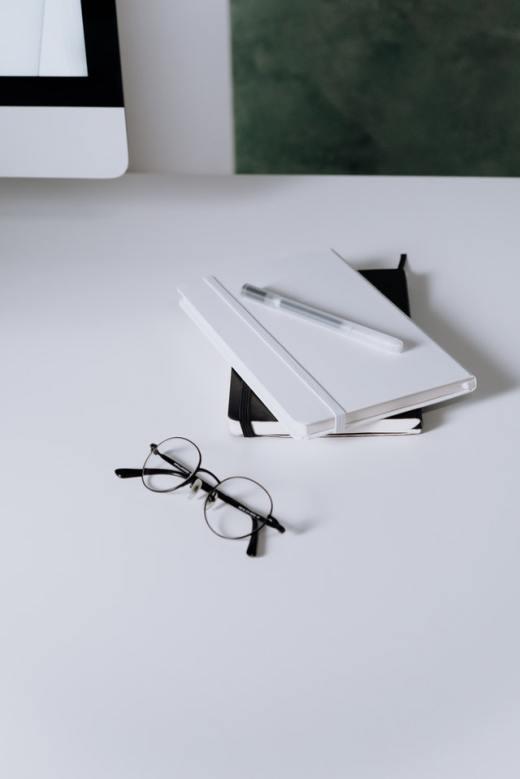 bril en notitieblok op bureau