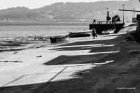 Señora en Combarro, sombras de casas, mar y gaviotas.