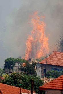A fire burns next to houses in the village of Mavriki near the town of Egio, Greece, on Wednesday.