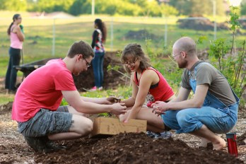 Keenan, Emily, and Tyler planting seed potatoes saved from last year