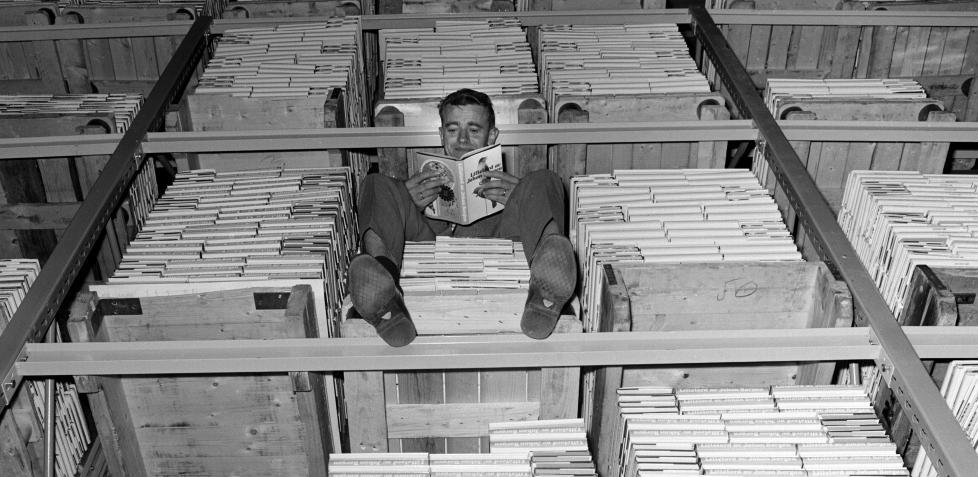MASSELITTERATUR: Siden 1961 har Bokklubben sendt ut mer enn 120 millioner bøker til norske lesere. Det er forlagene Gyldendal, Aschehoug og Pax som eier De norske Bokklubbene i dag. Her fra lageret i mai 1969 hvor direktøren den gangen, Knut T. Giæver, har satt seg til rette på en bokpall. Foto: Per Ervik/Aktuell/Scanpix