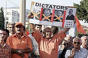 ØNSKER SEG EN ORANSJEREVOLUSJON: Opposisjonelle ønsker seg en revolusjon etter mønster fra Ukraina. Her holder en av dem opp en plakat med bilde av gamle sovjetdiktatorer. Nåværende president Alijev får også gjennomgå. Mer enn 2000 orangekledde deltok i denne demonstrasjonen i september.