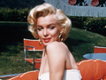 Marilyn Monroe in a white top and skirt on an orange armchair