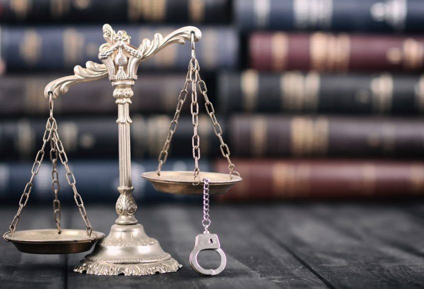 Scales of Justice and handcuffs on a black wooden background.