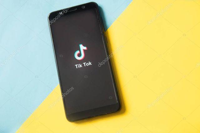 Tver, Russia - February 28, 2020 Tik tok logo on smartphone screen on blue and yellow background. Tik Tok icon. tik tok application. Tiktok Social media network. Space for text.