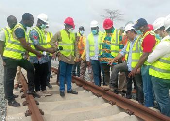 Mr John-Peter Amewu (standing on a sleeper) inspecting the Kojokrom-Manso railway line