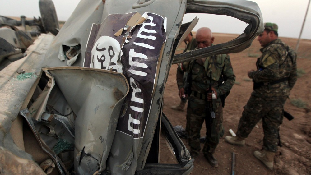 Peshmerga fighters inspect the remains of an ISIS car, after it was targeted by an American air strike in the village of Baqufa, north of Mosul, on August 18,2014. (AHMAD AL-RUBAYE/AFP/Getty Images)