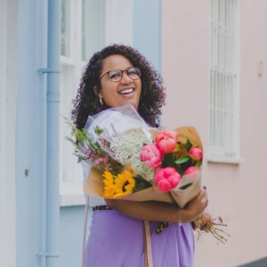 A close up of Ghenet standing, holding a bouquet of flowers.