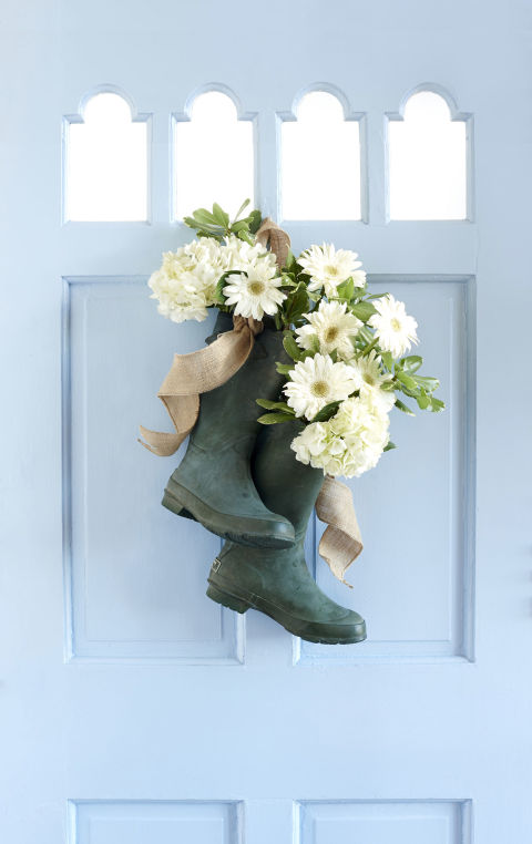 Install a metal grommet on the back of each rain boot. Loop a piece of burlap ribbon through grommets. Place a 3-inch-wide cylindrical vase in both boot heels; stabilize with tissue paper if needed. Fill vase with water and seasonal blooms. (We used a mix of hydrangeas and daisies.) Tie ends of ribbon together and hang on a nail. More from Country Living: • This Is the Most Beautiful Ribbon Made in America • Craft a Pretty Ruffled Wreath from Duct Tape • Watch and Learn How to Make a Floral Wreath