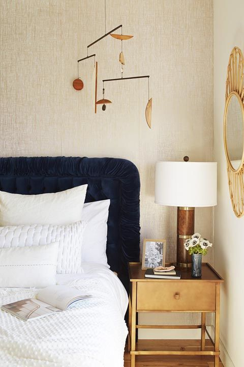 A formerly navy blue and white bedroom is given a new life when gold touches are added into the mix. Use accessories to achieve this look or paint a small piece of furniture, like the nightstand. Get the look: gold mirror, $102, amazon.com