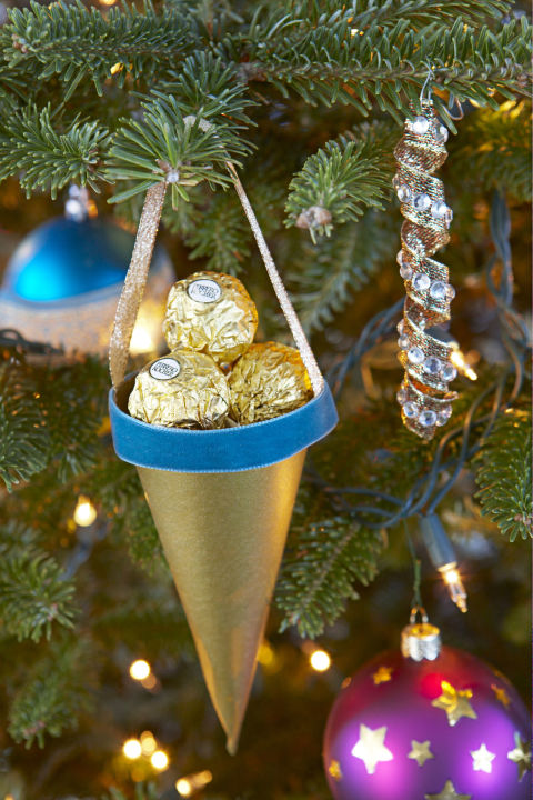 Paper cones filled with candy work as ornaments now and party favors later. Try wrapped peppermints, chocolate kisses or truffles for more color than mess. Get the tutorial » What you'll need:gold origami paper ($8 for100,amazon.com), velvet ribbon ($12,amazon.com)