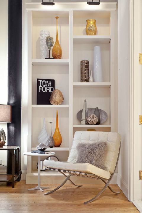 "Rather than jamming shelves full of knickknacks, Eisen opted for a minimalist look: Several books stand upright along with tall vases that fill the space without overcrowding it. She also added objects of various height and color to give the bookcase personality. Her favorite part about decorating this home? ""Turning wasted, unused space into a functional reading nook that can be enjoyed by many by simply adding a chair."" Steal this look with clusters of tall, affordable vases."