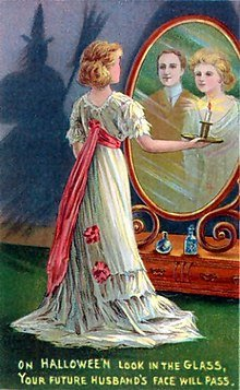 An early 20th century Halloween greeting card depicts a divination ritual in which a woman stares into a mirror in a darkened room to catch a glimpse of the face of her future husband. The shadow of a witch is cast onto the wall at left.