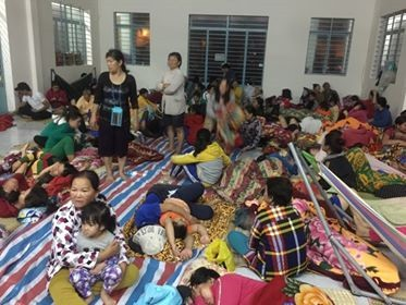 Người dân mang đồ đạc, chăn màn rồi trải chiếu nằm xếp lớp trên nền nhà. Cơ quan chức năng đã hỗ trợ mì tôm và nước nóng để dân lót dạ đêm khuya.