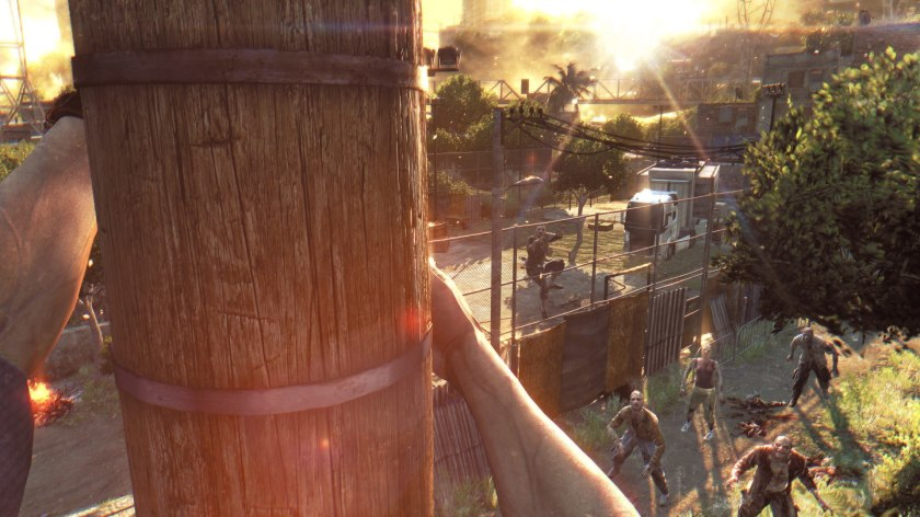 Dying Light. The player climbs a telephone pole and overlooks a horde of zombies below.