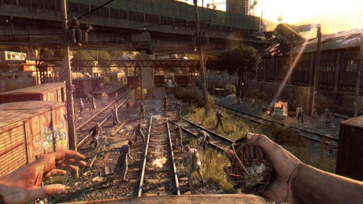Dying Light. The Player stands atop a train car overlooking a horde of zombies beneath them.
