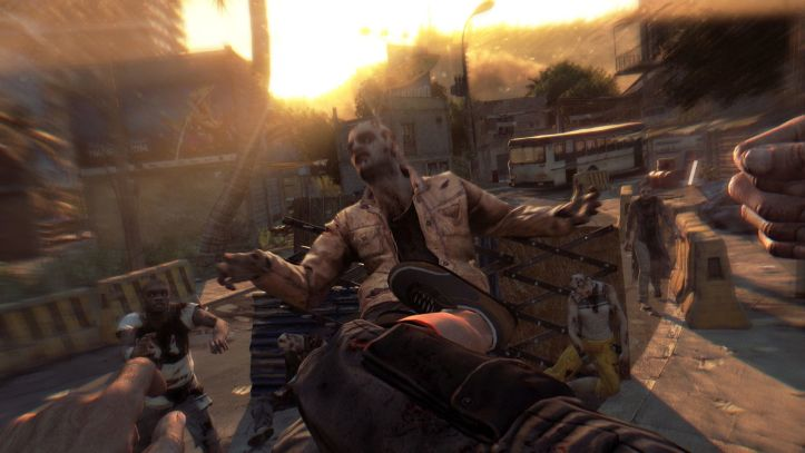 Dying Light. The player drop kicks a zombie into a set of spikes while more close in.