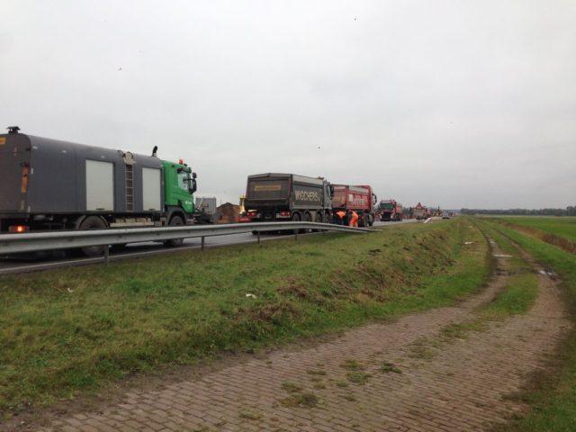 De vrachtauto's reden af en aan om het tempo van de asfalteermachine bij te benen.