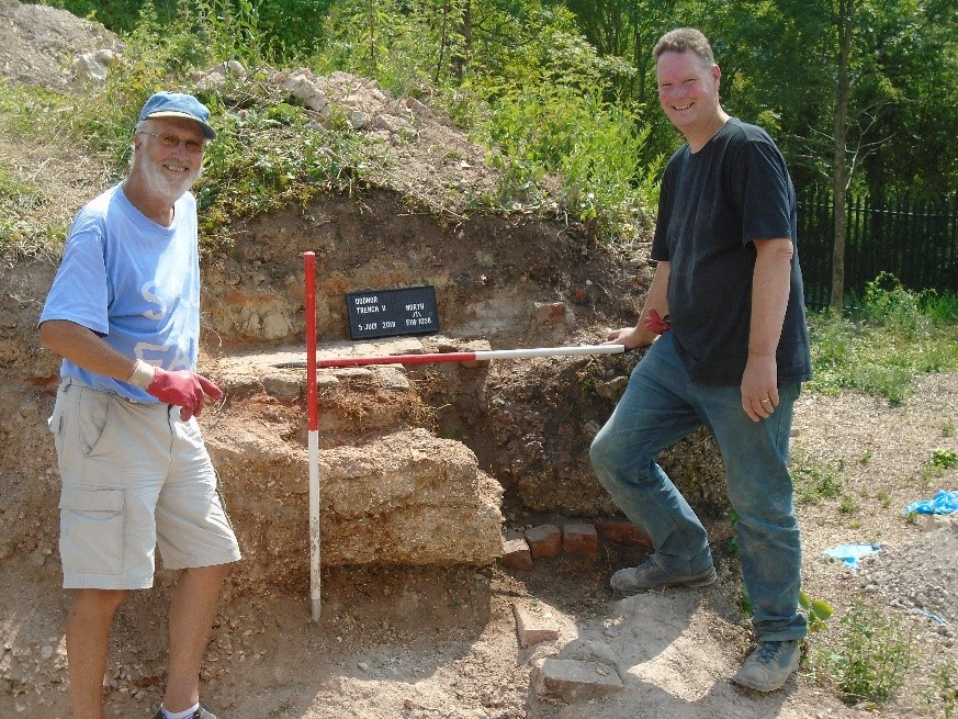 Chris and Tim reveal the later Chamber structure (dark grey concrete) which was butted up against the earlier Bottle Kiln (pink concrete).