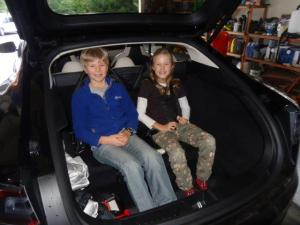Alexander und Julia sitzen hinten im Tessla...