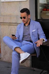 A model in a summer suit scrolling on his phone..