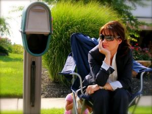 Addicted to email. Lady sitting at by a mailbox.