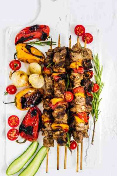 Lamb shish kabobs and roasted peppers on marble cutting board