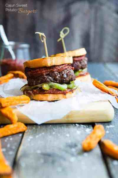 Cajun burgers on parchment paper surrounded by fries