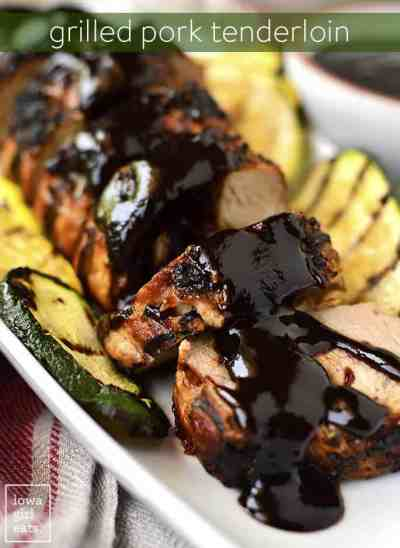 Grilled pork tenderloin slices with sauce and grilled zucchini on plate