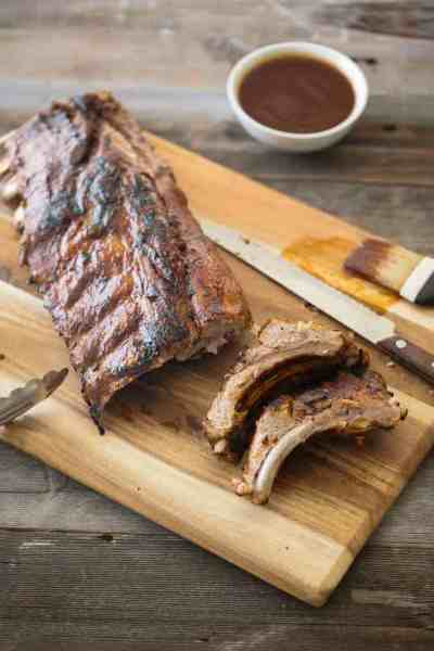 Barbecue ribs on cutting board and spiced rum pineapple sauce in white bowl