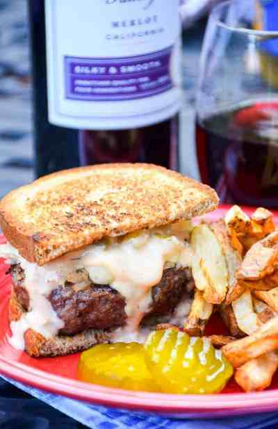 Grilled reuben burger, french fries, and pickles on plate