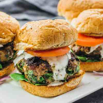 Greek burgers with feta, spinach, and tomato on plate
