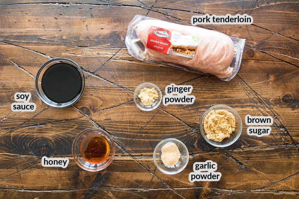 Overhead Image of ingredients on wooden board in glass bowls including soy sauce, honey, garlic powder, ginger powder, brown sugar and a pork tenderloin