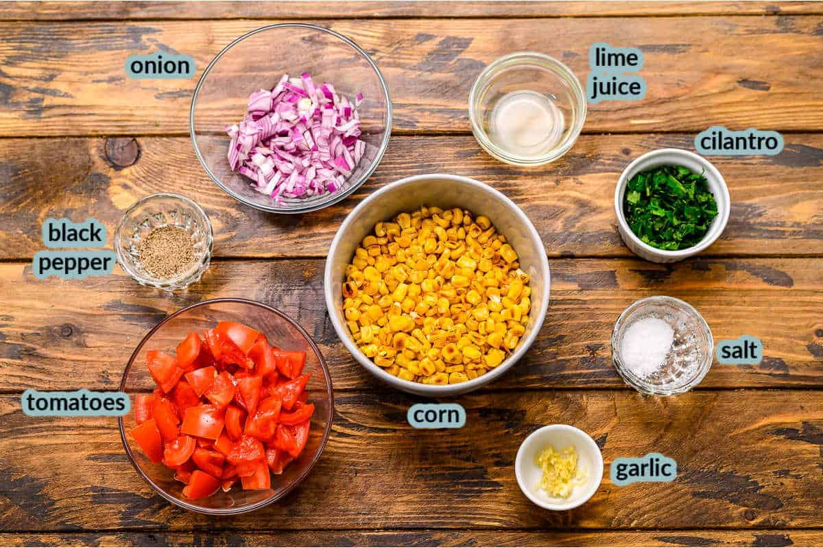 Ingredients for corn salsa including tomatoes corn onions cilantro salt lime juic pepper garlic
