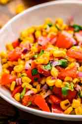 Bowl with grilled corn tomatoes onions and lime dressing