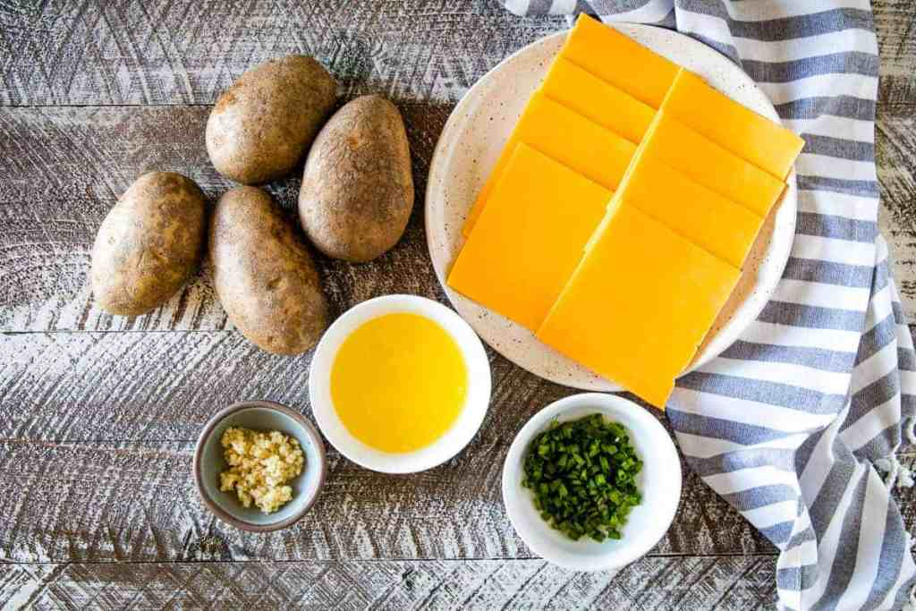Overhead image of potatoes, slices of cheese on plate, melted butter in bowl, minced garlic in bowl and chopped chives in a bowl.