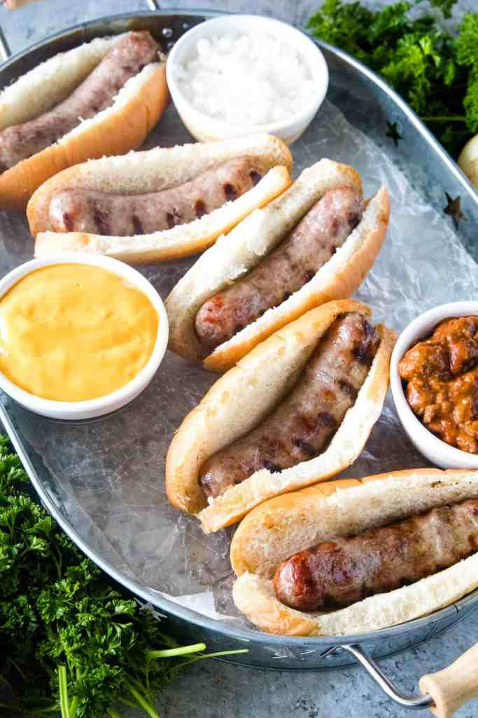 Brats in buns on silver serving tray with toppings next to them.