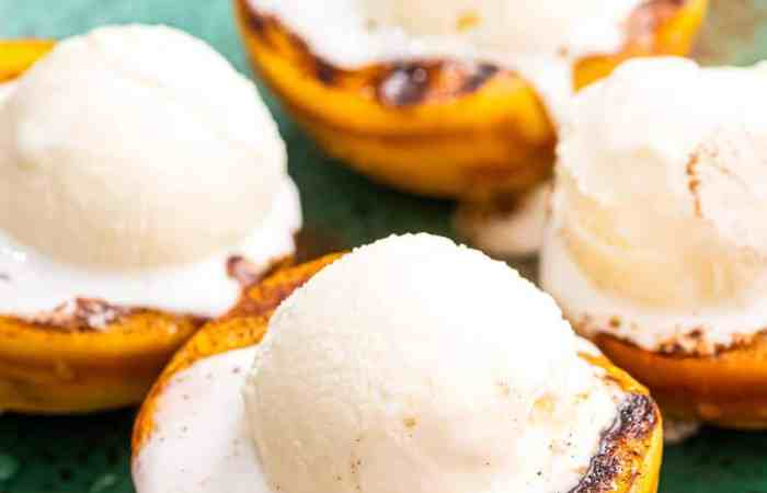 Close up image of four peaches halves that are grilled with a scoop of ice cream on top.