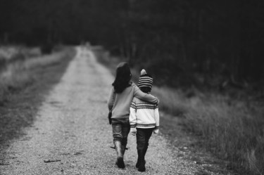 Two children walking away on a path with their arms around each other