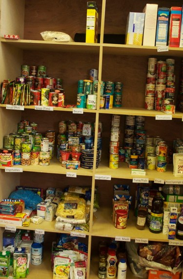 Food Bank Cupboard stocked with tinned and packet food