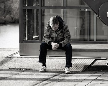 Man sitting on a bench looking down at the ground, as if in despair