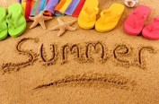 The word Summer written on a sandy beach, with beach towel, starfish and flip flops (studio shot - warm color and directional light are intentional). Note: extreme wide angle shot with curvature of field and focus on the word Summer.